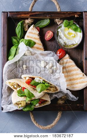 Pita bread sandwiches with grilled vegetables paprika, eggplant, tomato, basil and feta cheese served in wooden tray over gray stone background. Healthy fast food concept. Top view.