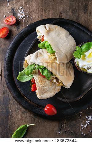 Pita bread sandwiches with grilled vegetables paprika, eggplant, tomato, basil and feta cheese served on black chopping board over dark wooden background. Healthy fast food concept. Top view space