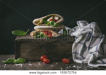 Pita bread sandwiches with grilled vegetables paprika, eggplant, tomato, basil and feta cheese on dark wooden box with kitchen towel over black background. Healthy fast food concept. Rustic style