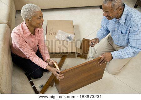 African couple assembling shelf
