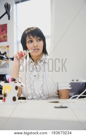 Indian businesswoman thinking in office