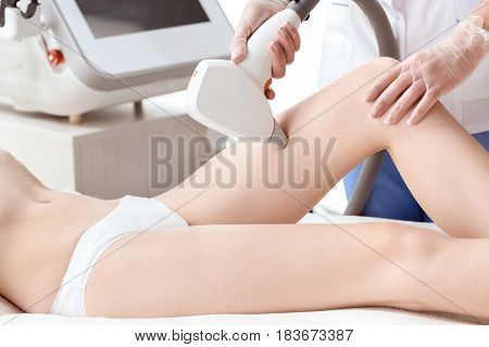 Partial View Of Young Woman Receiving Laser Hair Removal Epilation On Thigh. Laser Skin Care Concept