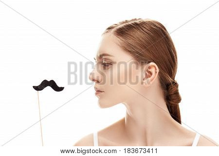 Profile Of Serious Young Woman Looking At Fake Moustache On Stick, Skin Care Concept