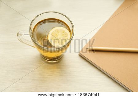 Cup of hot tea, notebook and pencil on wooden table