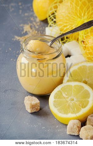 Jar of homemade lemon curd with spoon, whole and sliced lemons, sugar and zest over gray blue stone texture background. Close up