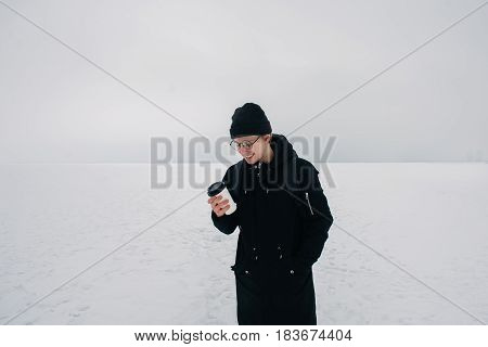 smiling young hipster guy dressed in black on the frozen pond with a cup of coffee