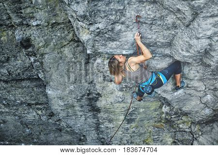 woman rock climber climbs on the cliff. rock climber climbs on a rocky wall. woman makes hard move