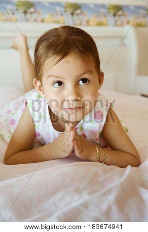 Hispanic girl praying on bed