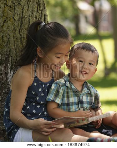 Chinese children reading storybook in park