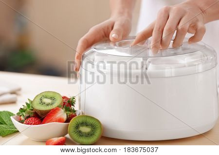 Woman preparing tasty yogurt at home, closeup