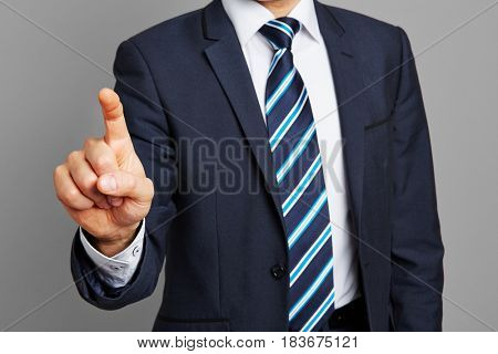 Hand of business man with raised index finger pressing a virtual touchscreen