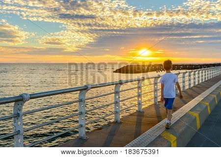 Boy walking along St. Kilda Jetty at sunset Melbourne Victoria Australia