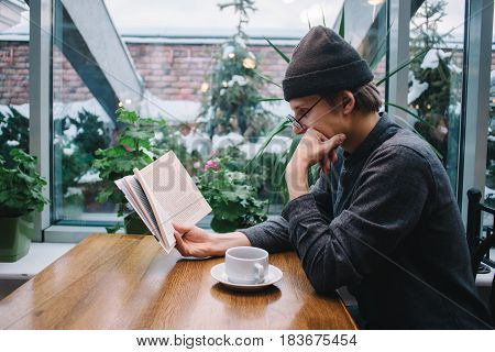 hipster young man with glasses and shirt carefully read a very interesting book in a nice cafe with green outside