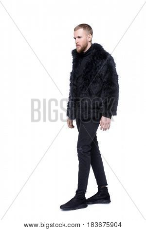 Fashion shot of a stylish bearded man wearing fur jacket. Full length portrait. Isolated over white.
