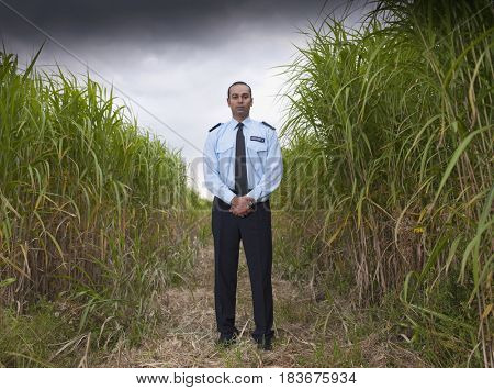 Asian man in uniform standing in field