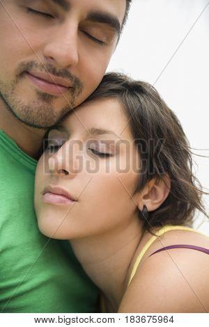 Hispanic couple hugging with eyes closed