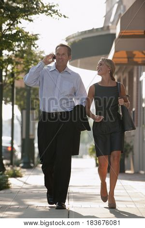 Caucasian businessman talking on cell phone and walking with co-worker