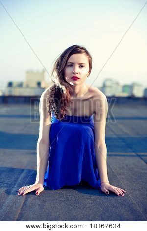 Attractive Girl Sitting In A Blue Dress