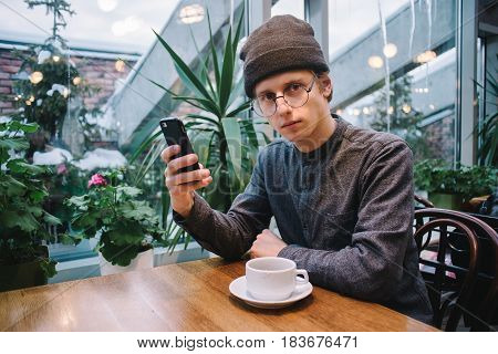 beautiful young student uses a mobile phone in a nice cafe near the window. tea is on the table and outside greenhouse