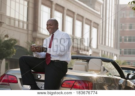 Black businessman text messaging on cell phone outdoors