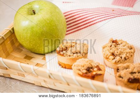 Professional baking. Magnificent portioned tartlet cakes with sweet stuffing. Background of wicker basket, white dish towel and green apple