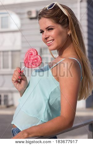 Girl Holding A Lollipop. Beautiful Happy Blond Girl In The Street. Young Woman Eating A Piece Of Can