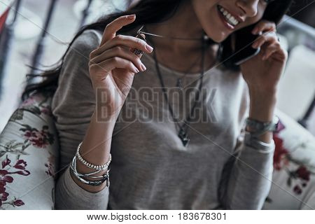 Pleasant talk. Close-up of young woman playing with her necklace and smiling while talking on the smart phone