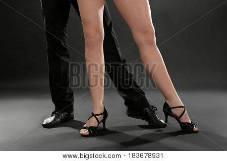 Legs of young dancers on dark background