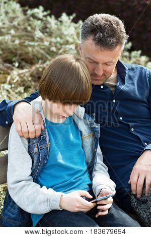 Father with teen son using smart phone outdoor together. Young boy with his father in spring park.