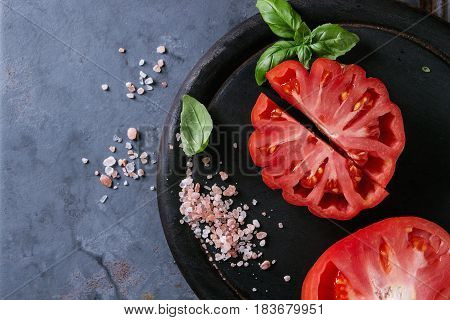 Whole and sliced organic tomatoes Coeur De Boeuf. Beefsteak tomato with pink salt and basil on black wooden chopping board over blue gray metal texture background. Top view with space.