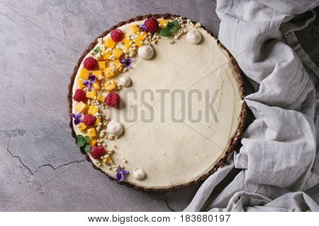 Homemade chocolate tart decorated by mango, raspberries, mint, puffed rice and edible flowers served with textile linen over gray texture table. Top view with space. Comfort food concept.
