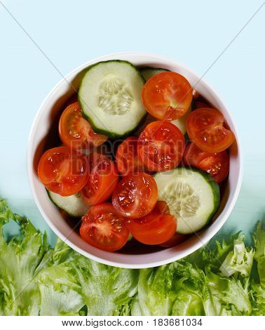 Food background. Salad with tomatoes and cucumbers grows on a herbs field. Space for text