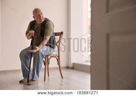 Senior man with coins sitting on chair in empty room. Poverty concept