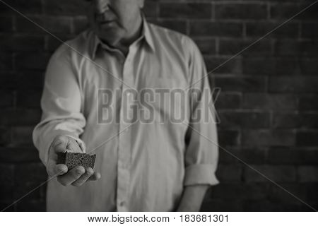 Senior man with piece of bread near brick wall. Poverty concept