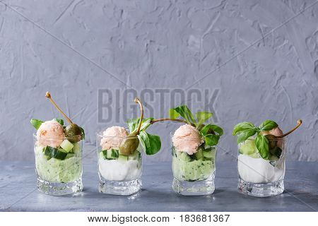 Verrines appetizer with salmon pate, red caviar, cucumber, cream cheese, herbs, capers in glasses served over blue gray texture background.