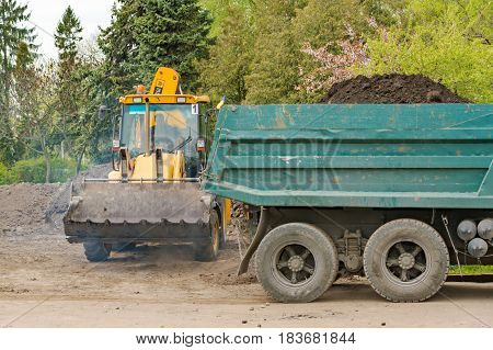 The tractor loaded the earth into the lorry. Ternopil. Repair of the park. Land works. 04 27 2017