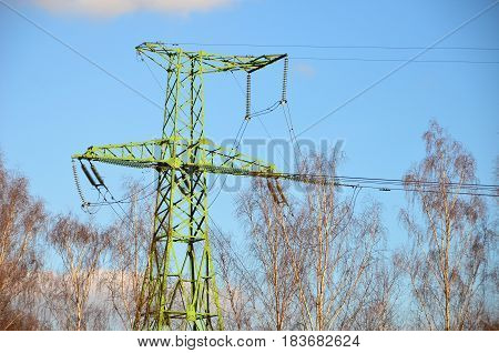 Electrical transmission bright green tower. High voltage. Blue sky background.