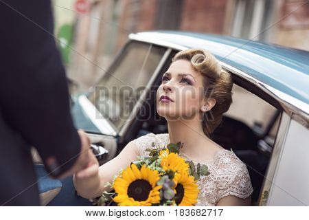 Beautiful young bride sitting in a wedding dress in a retro old car holding a sunflower bouquet while groom is helping her get out of the car