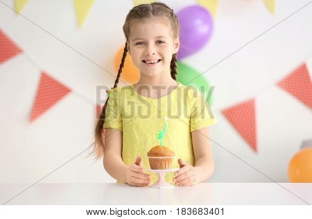 Cute little girl with birthday cake at home