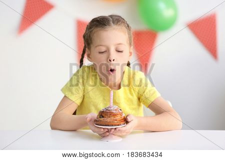 Cute little girl blowing out candle on birthday cake at home