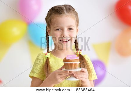 Cute little girl with birthday cake on blurred background