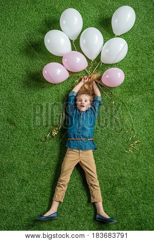 Top View Of Excited Little Girl Holding Balloons On Green Grass