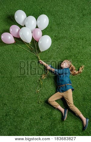 Top View Of Little Girl Holding Balloons On Green Grass