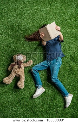 Top View Of Little Girl With Teddy Bear Reading Book While Lying On Grass, Education Kids Concept