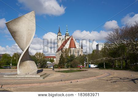 MAGDEBURG, GERMANY - APRIL 19, 2017: Flag monument and St. Johannis-Church on the banks of the river Elbe in Magdeburg. The St. Johonnis-Church in Magdeburg is a former church building and has been used since 1999 for concerts and events.