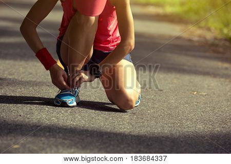 young fitness woman runner tying shoelace before run on sunset beach