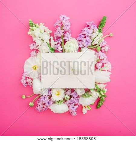Flat lay frame with paper envelope and beautiful flowers on pink background. Top view