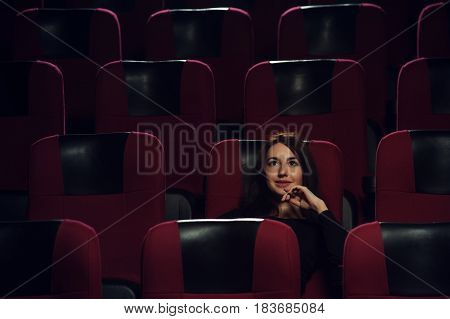 Young attractive brunette woman sitting in empty cinema hall and watching movie. Cinema, entertainment and leisure concept.