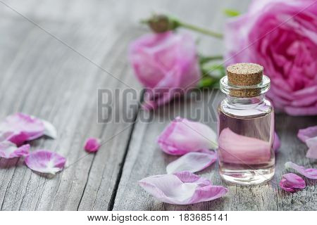 Glass vial with rose essential oil and flower of pink rose on a wooden background with space for text
