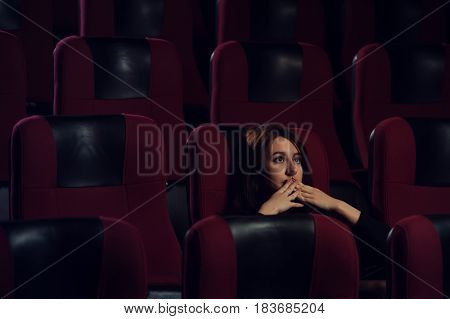 Young scared girl watching horror movie in cinema theater. Beautiful brunette girl sitting alone in empty hall. Cinema, entertainment and leisure concept.